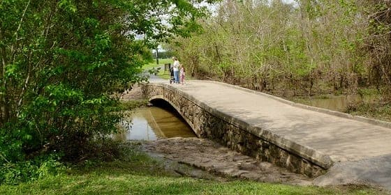 A bridge leading over water separating the two different parks.