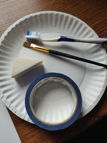 Paint brush, toothbrush, sponge, paper plate and painters tape