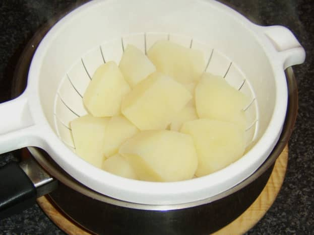 Potatoes are drained through a colander