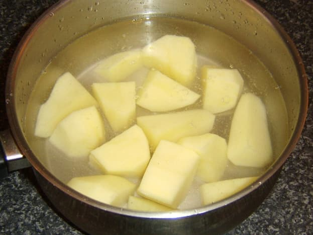Potato is peeled, chopped and added to cold, salted water