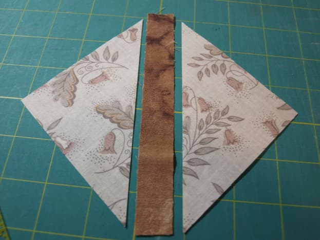"""1. Cut the 5"""" inch square of light fabric in half, diagonally and lay the dark strip in between."""