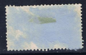 This is the back of a stamp that has been removed from an envelope.  There is still a lot of paper attached to the stamp.  This is not desirable.