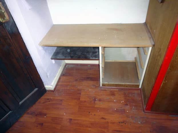 The carcass of the old built-in bedside table, repurposed in the alcove, was fitted before the laminate floor.  Therefore, in removing this cupboard means adding a new section of laminate flooring