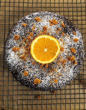 Espresso chocolate cake with chocolate glaze, powdered sugar, and cookie crumbles on top