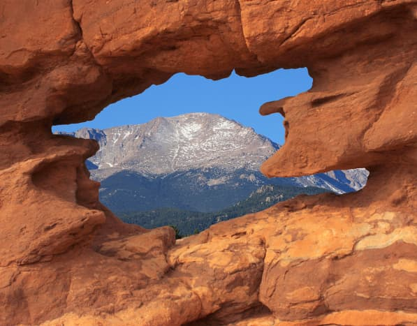 Pikes Peak mountain, America's Mountain, through the red rocks of the Simese Twins rock formation in Garden of the Gods park located in Colorado Springs, CO.