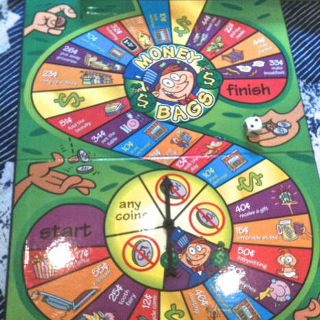 The money game board. It is a combination rolling dice/spinner game. You land on a space that might say you earned 25 cents. You choose the coins.