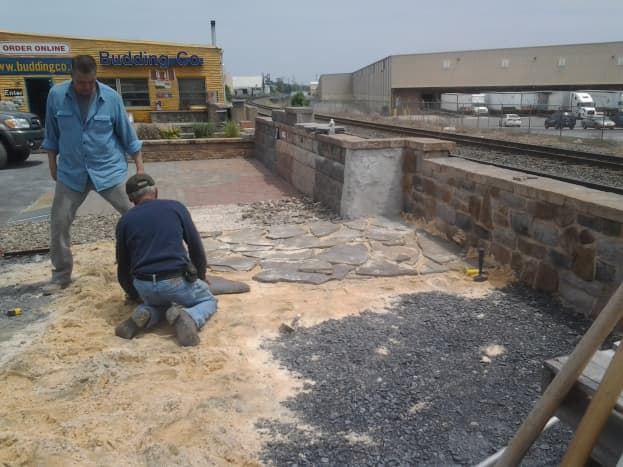 a. Building a display pavement out of varied sizes of flagstone slabs.