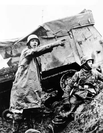 German troops advance past an abandoned American half-track early in the attack in the Ardennes forest December 1944.