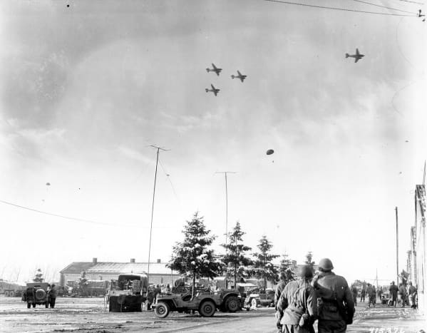 Photo taken by a U.S. Army Signal Corps photographer on December 26, 1944, in Bastogne, Belgium as troops of the 101st Airborne Division watch C-47s drop supplies.