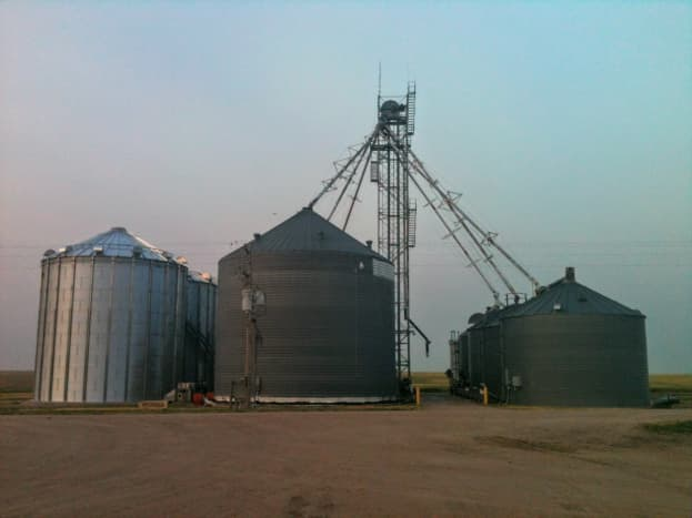 The pit and leg system on this bin cluster demands a clear, compact driveway for dumping or receiving loads of grain. The bins on the left are not part of the same system.
