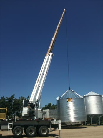 Here you can see why the wheels and bigger outriggers make this crane more stable than most boom trucks. It is lifting a 4,000 bushel bin (18-foot diameter) in preparation for setting it onto a hopper.