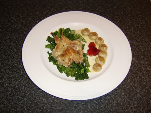 Casseroled quail on braised savoy cabbage with redcurrant jelly