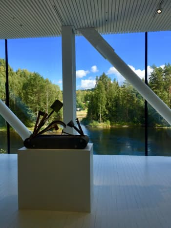 """Large panoramic windows open up to lots of natural light and beautiful views of nature and the trout river, Randselva. In the foreground is Pedro Reyes's sculpture """"Navaja Suiza VIII (Swiss Army Knife VIII)"""", 2014."""