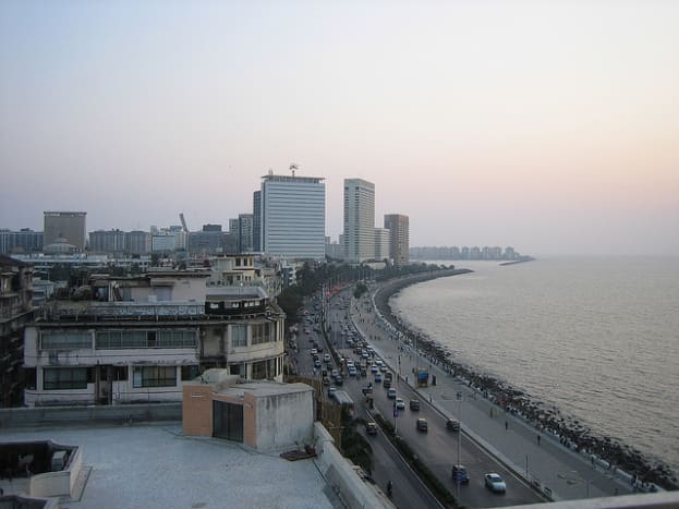 View of Marine drive, to the far right can be seen the walkway running all along marine drive with people having a stroll and many people sitting on the parapet of the wall that runsall along the walkway