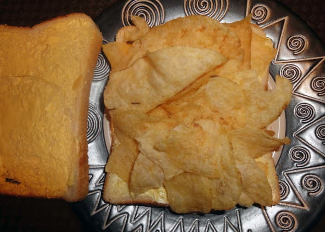 One packet of crisps on a slice of buttered bread