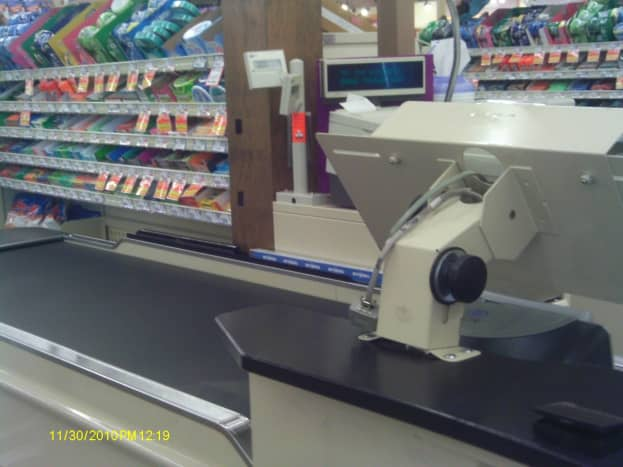 A grocery store uses a conveyor belt to move items toward the cashier for checkout.