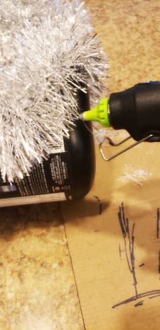 Hot glue your silver garland around your old container.