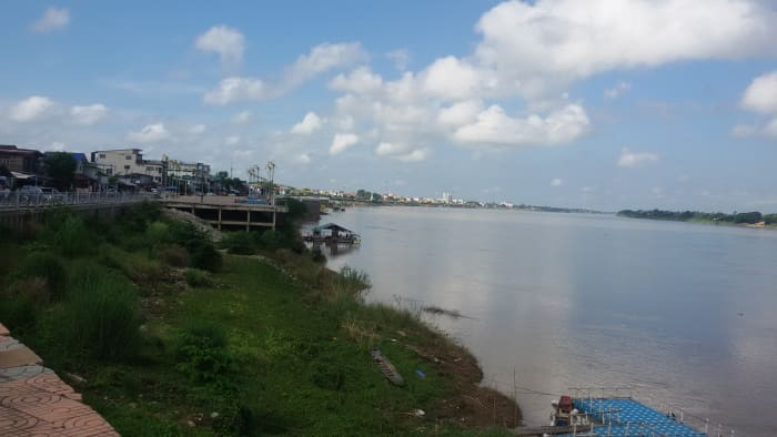 Nong Khai Mekhong Riverside Promenade with Phra That Chedi in the foreground and Thai-Laos Friendship Bridge in the distant background.