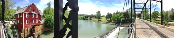 Panorama view of mill, river, and bridge.