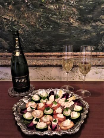 Platter of hors d'oeuvres with smoked trout spread and sparkling wine ready to enjoy
