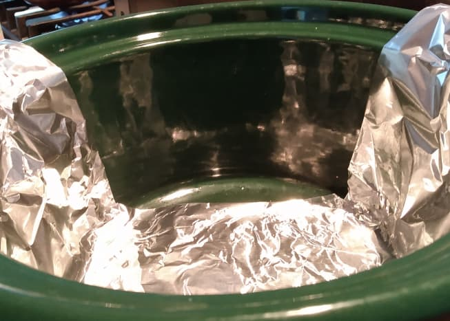 To make enchiladas in a slow cooker, you first need to make a sling with foil.