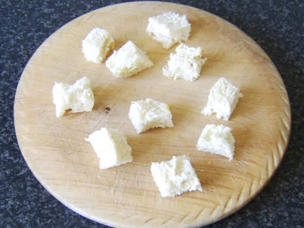 Bread with crusts removed is chopped in to one inch cubes