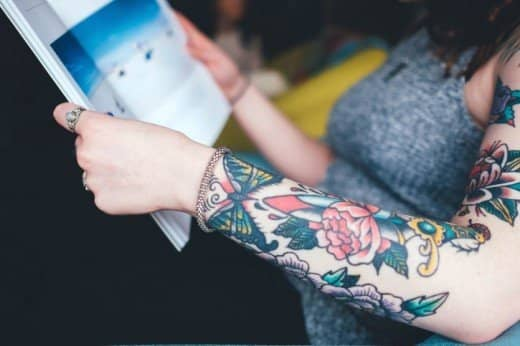 Flower tattoos come in a range of designs such as this one alongside a butterfly.