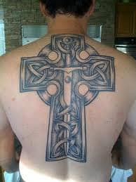 A tattoo of a sword and a cross.