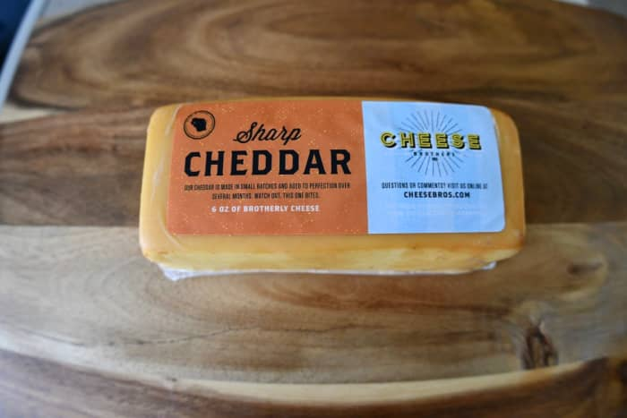 A sharp cheddar with many delightful surprises. It has a slight smoky taste. It's squishy, it has a pleasing aroma, and the inside looks different than the outside.