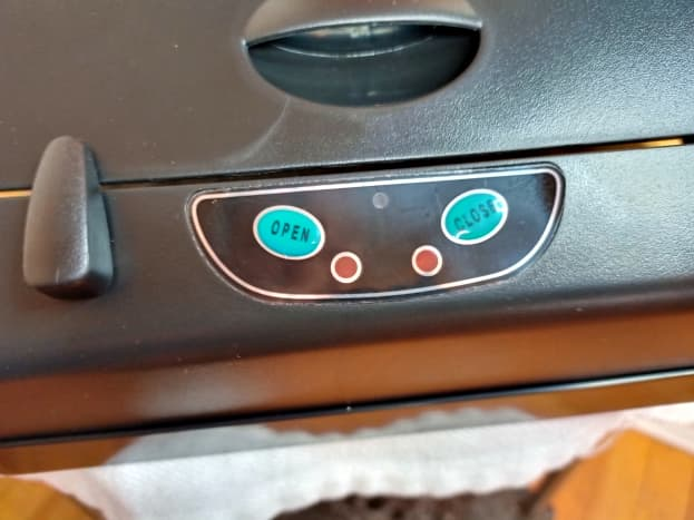 A view of manual controls, sensor, and switch used to prevent a dog from opening the trashcan lid