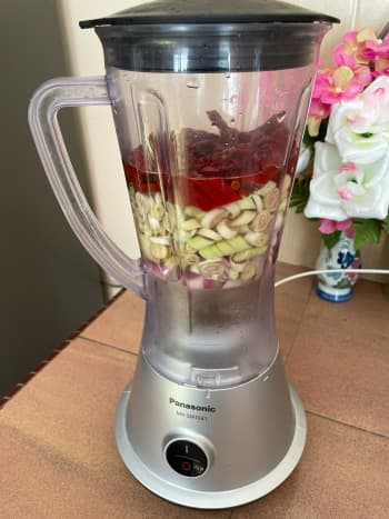 In a blender, combine the shallots, ginger, lemongrass, dried red chiles, garlic, turmeric, and water.