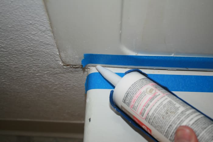 Start at one edge and begin squeezing and hold the trigger, dragging the gun across the seam to get as even a layer of caulk as you can.