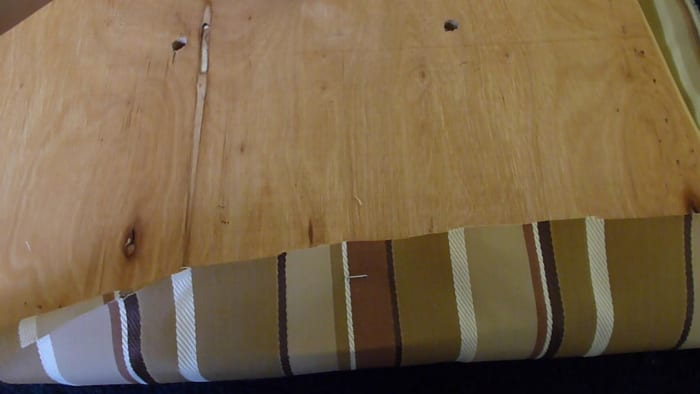 Pulling tightly, tack the fabric to each side of the wooden base with the staple gun.
