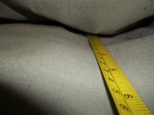 Locate back side of couch frame underneath the top back cushions.