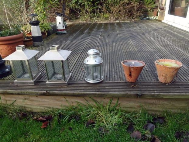Mood setting outdoor candle lanterns and pots for decking.