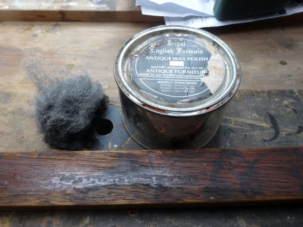 Applying coloured beeswax polish with wire wool.