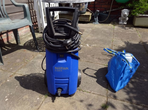 My Nilfisk C110.4 on my patio, with a blue bag of accessories to the right; the bag not supplied by the manufacturer.