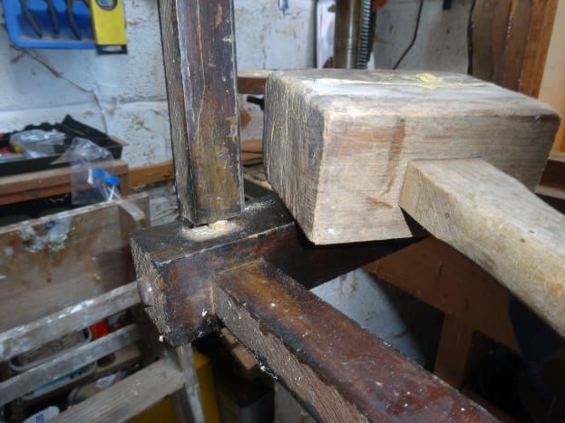 Using wooden mallet to gently separate leg joints far enough to apply glue in the gaps.