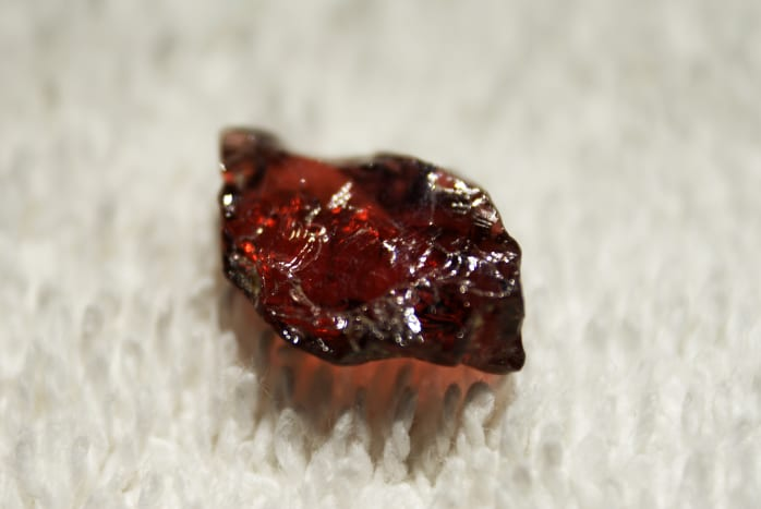 This is a raw cut piece of garnet. Its blood red colour makes it highly popular with jewellery makers.