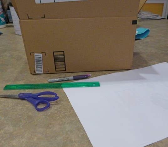 Get your craft supplies ready. We used a piece of cardboard box, some large white paper, scissors, and a pencil. Simple!