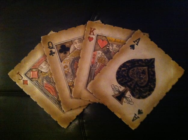 A decoration showing four playing cards.  Decorations like this can be used in playing card collections.