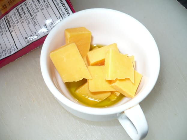 In an oven proof cup add the garlic infused olive oil, one ounce of cheddar cheese,and tablespoon of butter.
