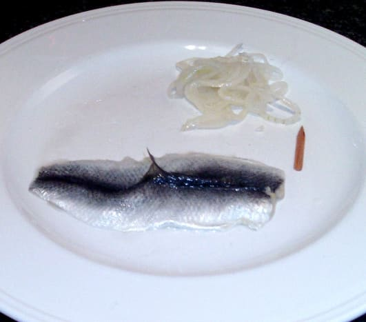 Unwrapped pickled herring or rollmop with dangerously protruding fin