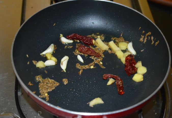 Step one: Heat ghee or butter in a pan. Add cumin seeds. Let them sizzle. Throw in ginger, dry red chili, and garlic.