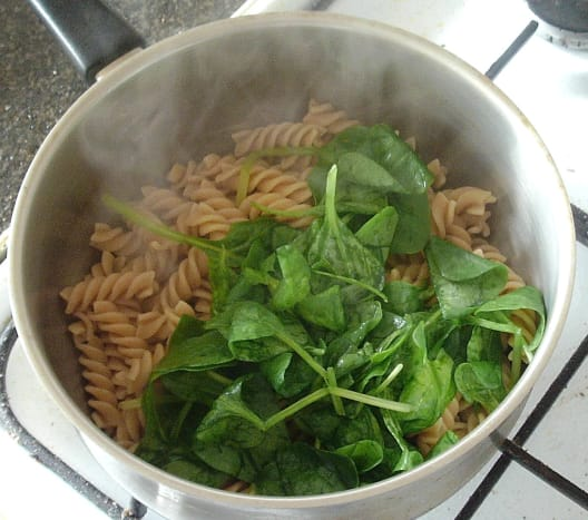 Baby spinach leaves are added to steaming hot pasta