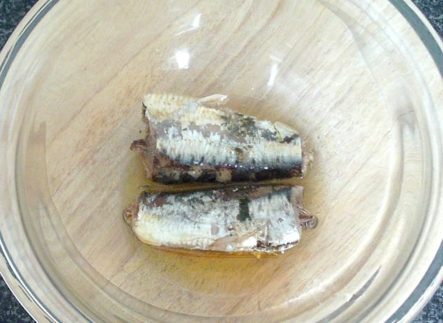 Canned sardines in olive oil are added to a large mixing bowl