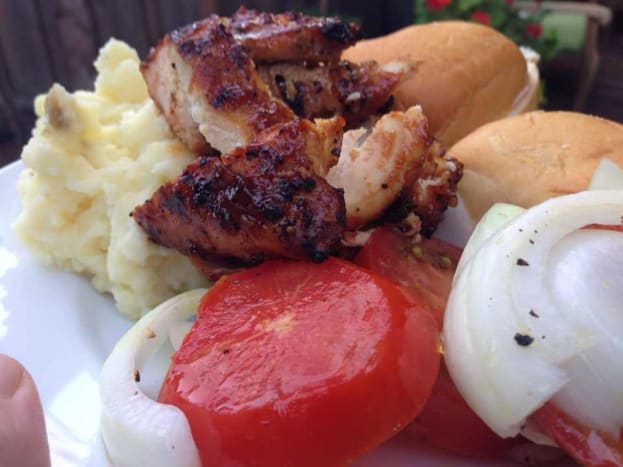 BBQ chicken served with mashed potatoes and tomato and onion salad