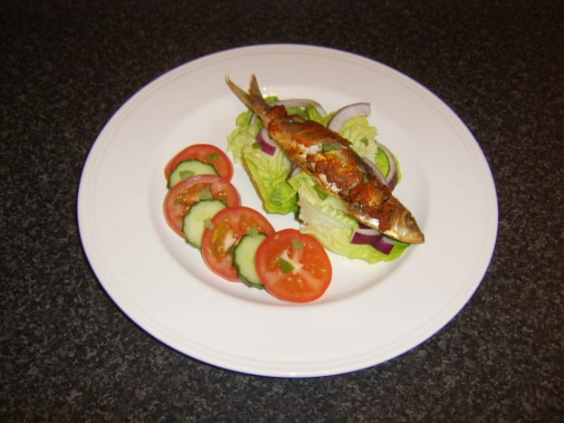 Red pesto sauce is rubbed on to the sardine before it is baked and served with a simple salad.