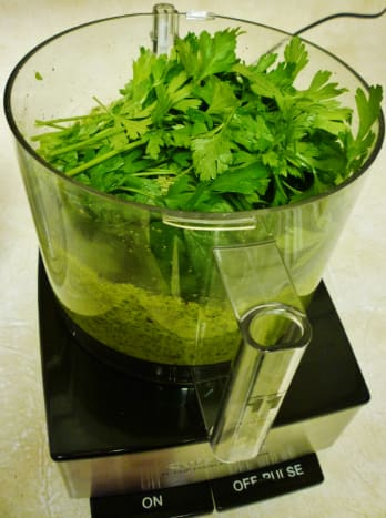 Filling the mixing bowl with the fresh ingredients for the pesto.
