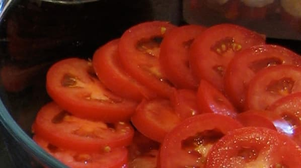 Sliced tomato layer in the casserole dish.